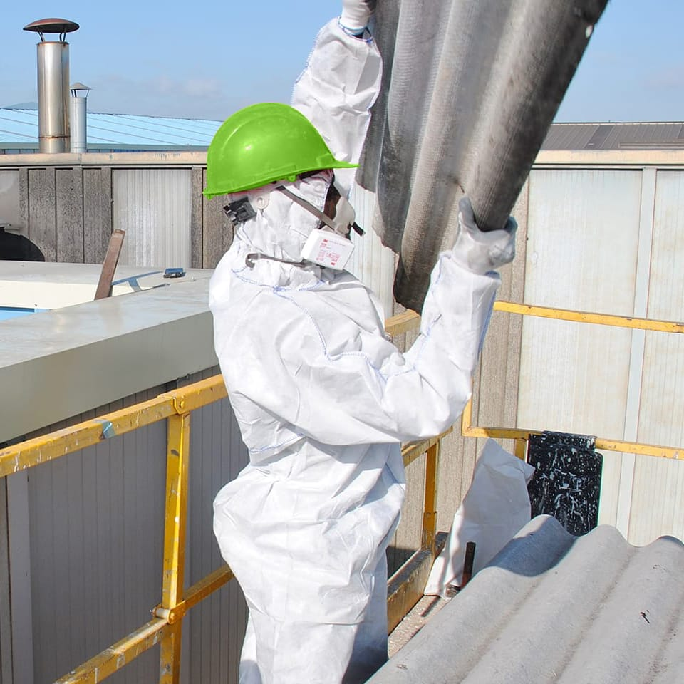 HAZMAT working removing roof panels that contain asbestos